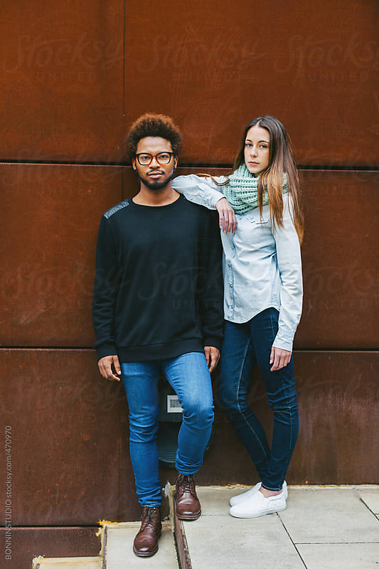 Portrait of young multi ethnic couple standing on stairs in outdoors. by BONNINSTUDIO for Stocksy United