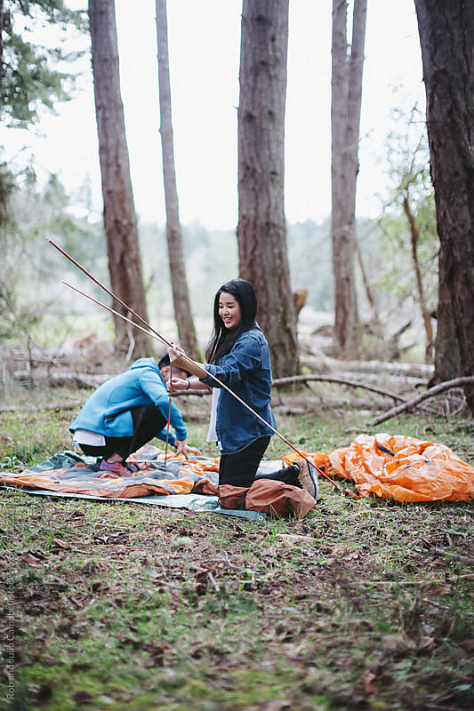 Young asian couple setting up tent together in the forest by Rob and Julia Campbell for Stocksy United