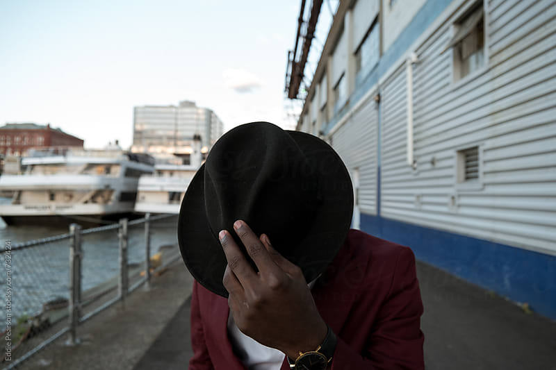 Young dapper male fixing his hat by Eddie Pearson for Stocksy United