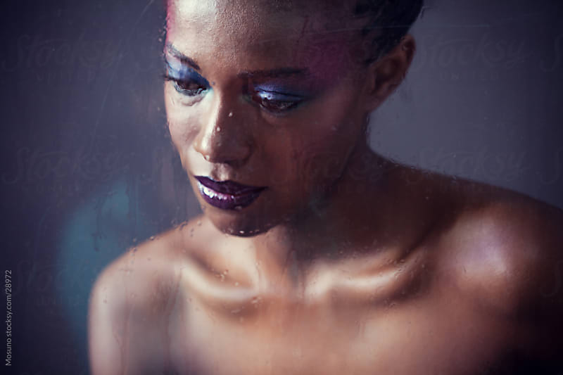 Beautiful african woman posing behind wet window. by Mosuno for Stocksy United