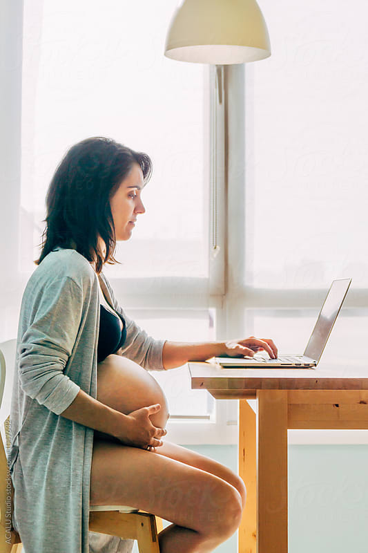 Pregnant working with the computer in the living room by ACALU Studio for Stocksy United
