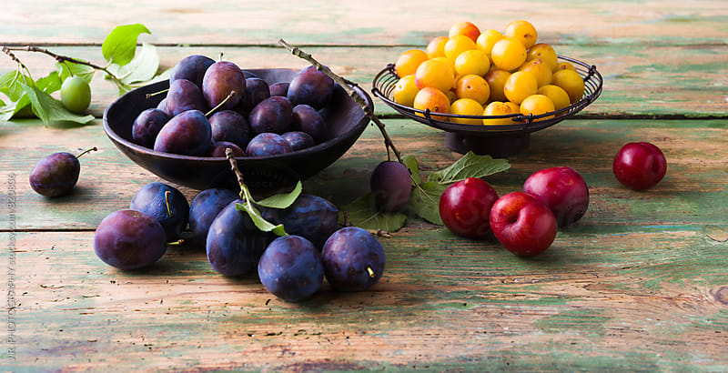Plums and mirabelle in baskets on a wooden table by J.R. PHOTOGRAPHY for Stocksy United