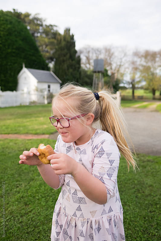 Cheeky kid eating a donut by Rowena Naylor for Stocksy United