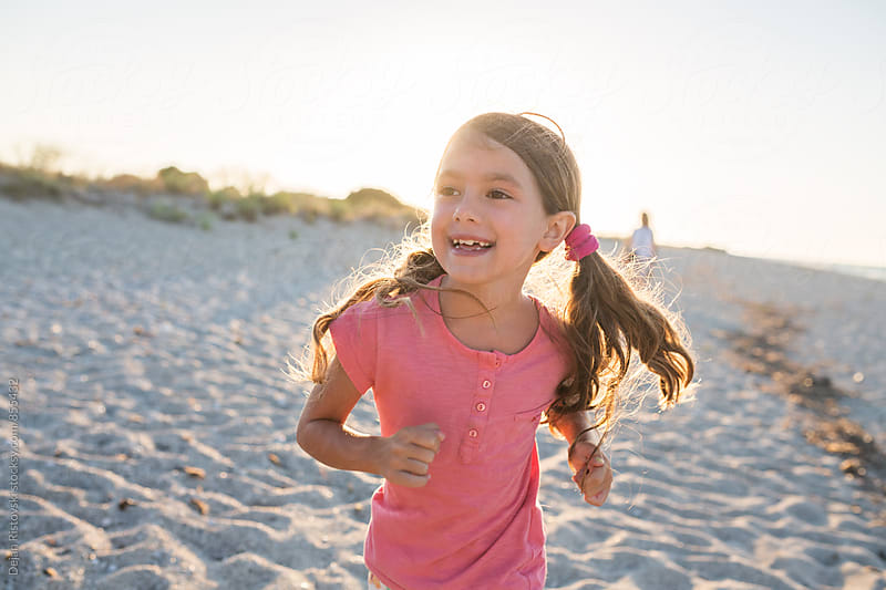 Sweet girl running on the beach. by Dejan Ristovski for Stocksy United
