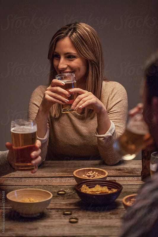 Woman Laughing and Drinking Beer With Friends by Mosuno for Stocksy United