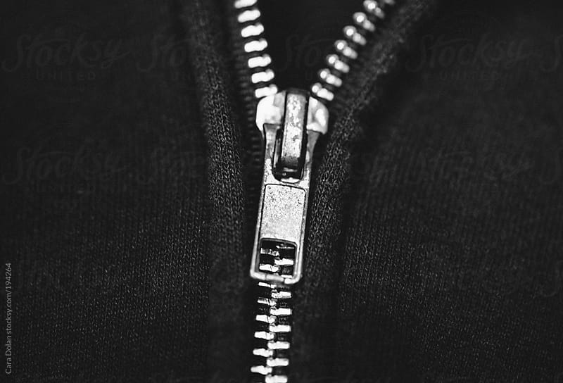 Detail of the zipper of a black hooded sweatshirt by Cara Dolan for Stocksy United