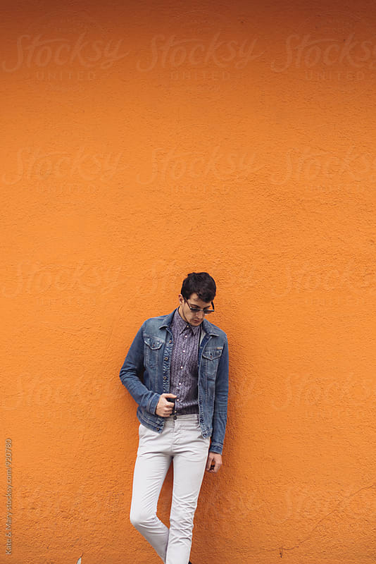Portrait of stylish man on orange wall by Kate & Mary for Stocksy United