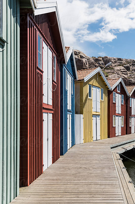 Colourful Swedish wooden fishermen huts in a harbour by Lior + Lone for Stocksy United