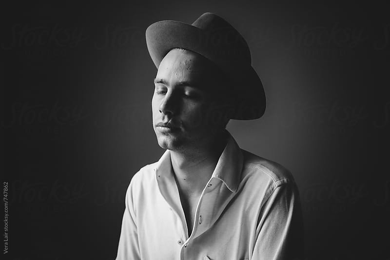 Portrait of a young man with a hat by Vera Lair for Stocksy United
