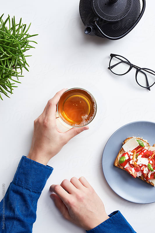 Man's hands with tea in glass and veg toast by Martí Sans for Stocksy United