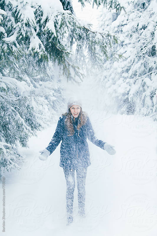 Happy woman enjoying falling snow in winter forest by Borislav Zhuykov for Stocksy United