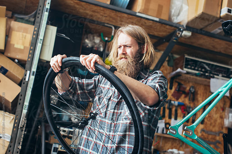 Blond Millennial Hipster Assembling Tire on Wheel of Fixed Gear Bike in Bright Workshop by VISUALSPECTRUM for Stocksy United