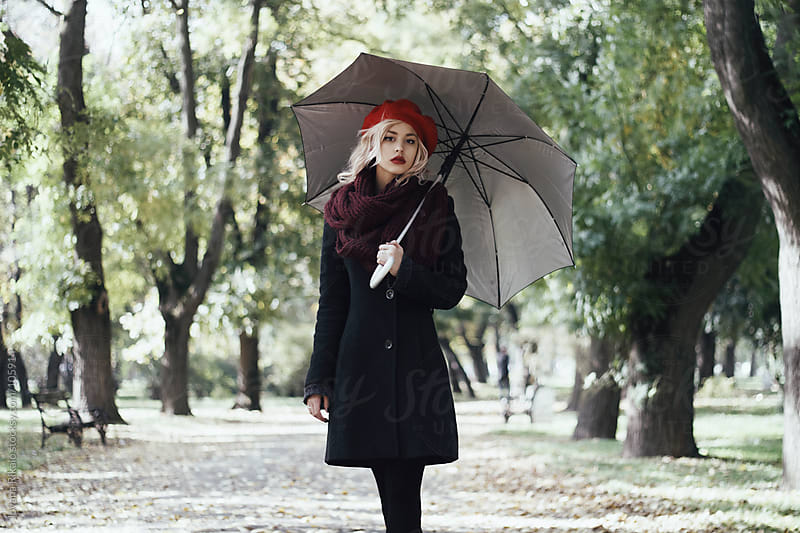 A beautiful girl holding umbrella in the park by Jovana Rikalo for Stocksy United