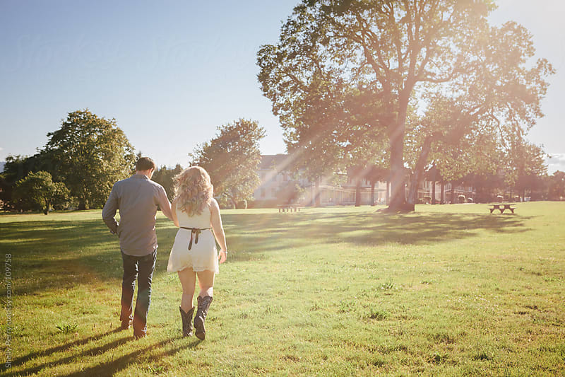 Young couple walking hand in hand in the park by Shelly Perry for Stocksy United