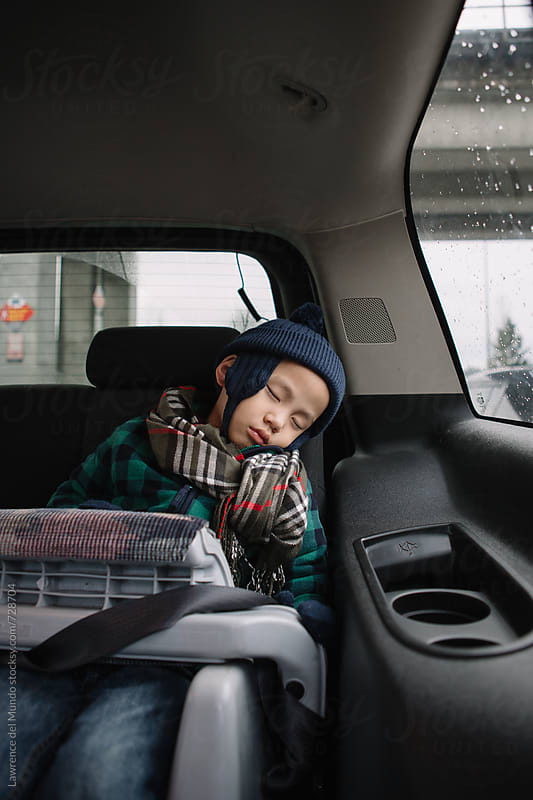Young child wearing a seatbelt in car booster seat falls asleep during a road trip by Lawrence del Mundo for Stocksy United
