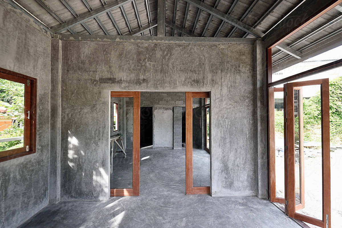 Empty interior of an unfinished concrete and wood home under ...