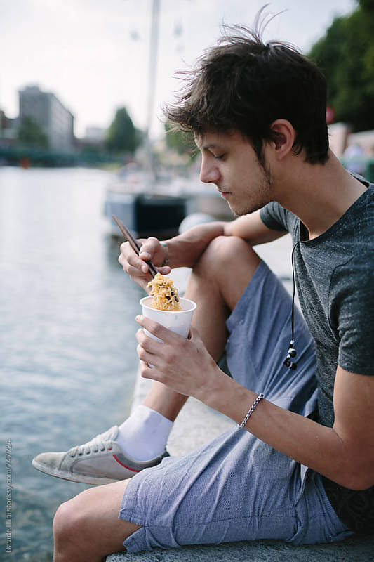 Young man eating noodle outdoors by Davide Illini for Stocksy United