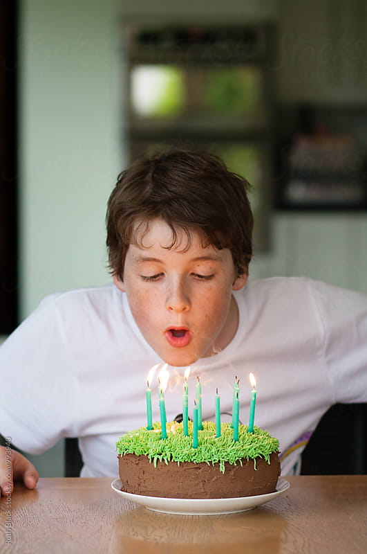 Boy blowing out birthday cake candles by Ruth Black for Stocksy United