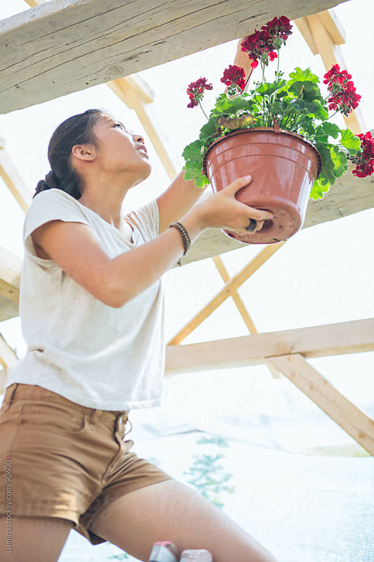 Woman Hanging a Potted Flower by Lumina for Stocksy United