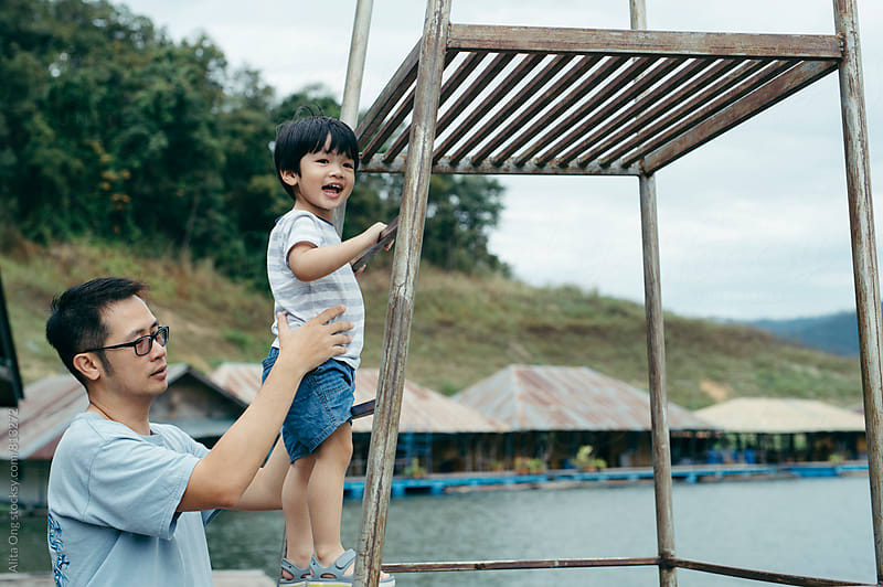 Father and son at a pier by Alita Ong for Stocksy United