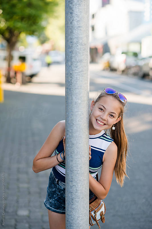 Early Teen Girl Smiling Behind Post by Ronnie Comeau for Stocksy United