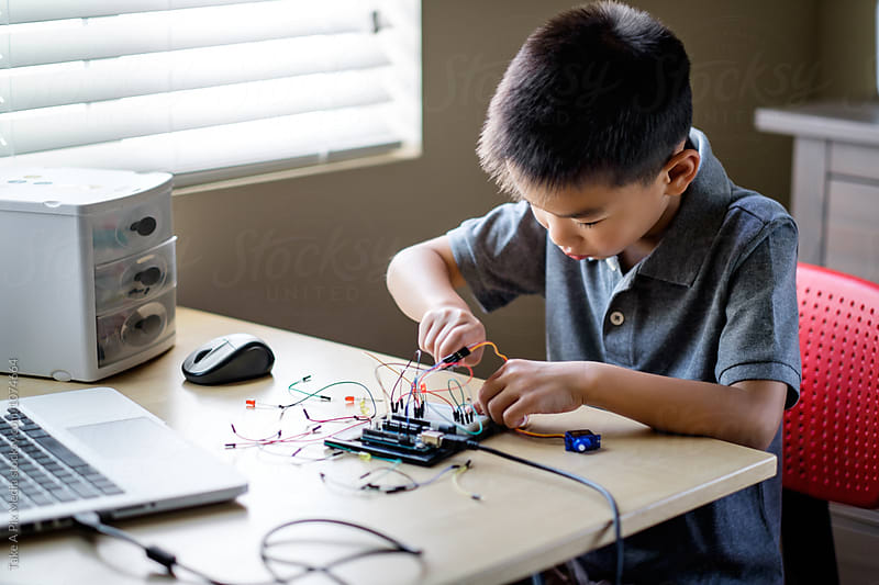 Asian kid working on an electronic project at home by Suprijono Suharjoto for Stocksy United
