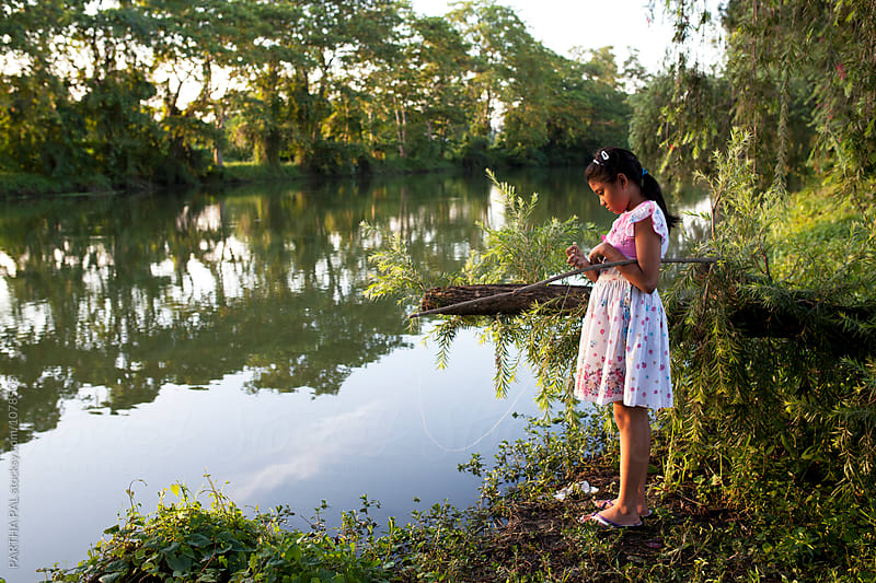 A teenage girl enjoying fishing activity by PARTHA PAL for Stocksy United