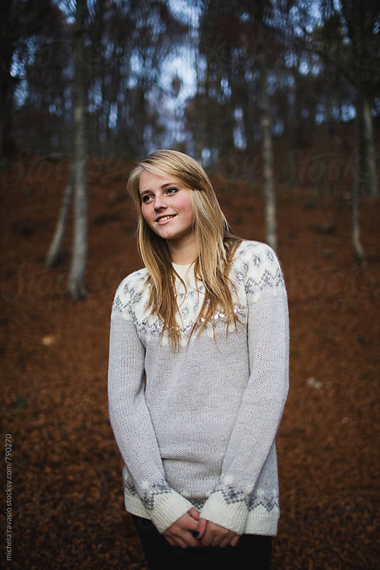 Portrait of a smiling young woman standing in the woods by michela ravasio for Stocksy United