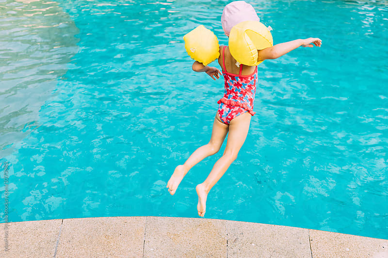 Cute little girl jumping into swimming pool by Maa Hoo for Stocksy United