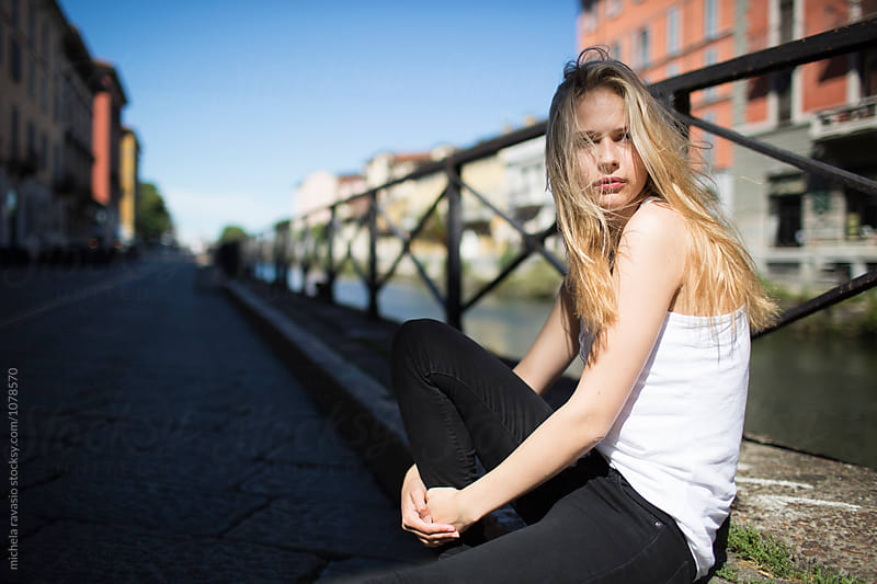 Blonde girl sitting on a sidewalk by michela ravasio for Stocksy United