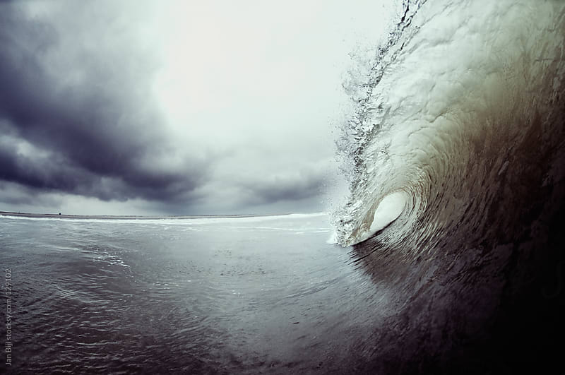 breaking wave with clouds in the backdrop by Jan Bijl for Stocksy United
