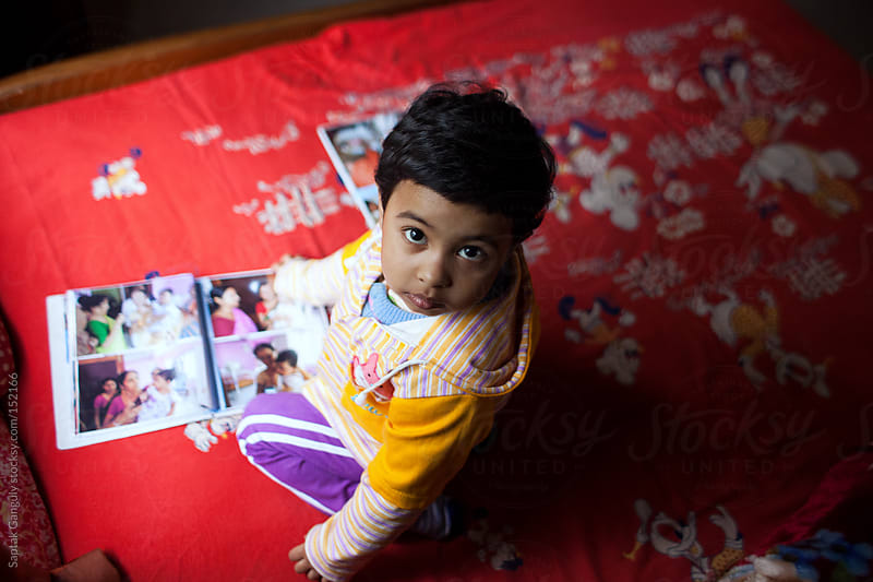 Toddler with family photo album looking at camera,top view by Saptak Ganguly for Stocksy United