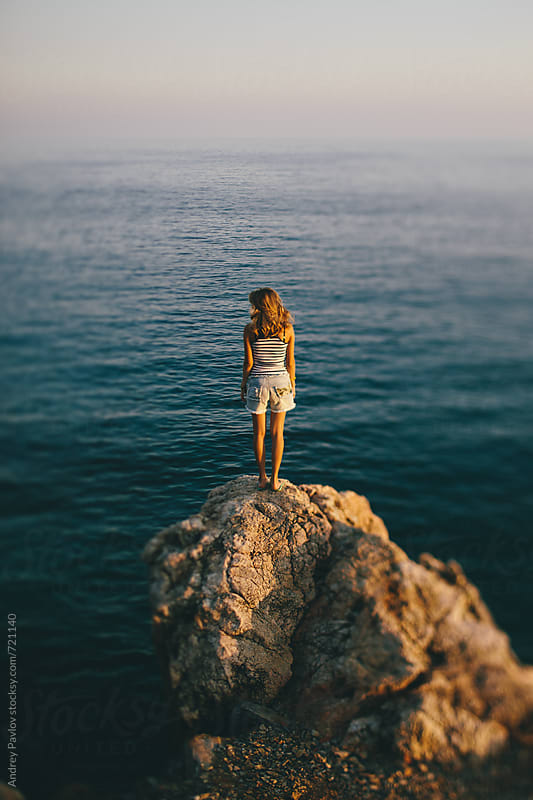 Alone woman standing on a rock by Andrey Pavlov for Stocksy United