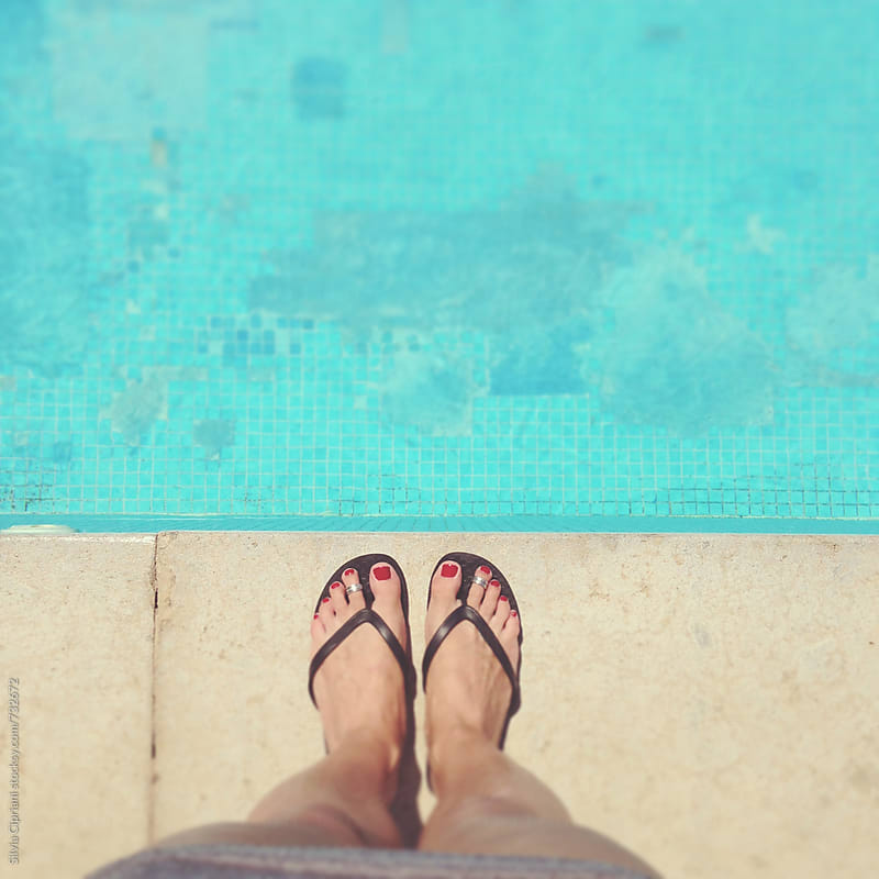 Woman's feet on the pool edge by Silvia Cipriani for Stocksy United