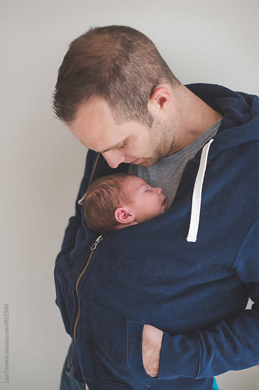 Father carrying his newborn son on his chest covered with a jumper by Lea Csontos for Stocksy United