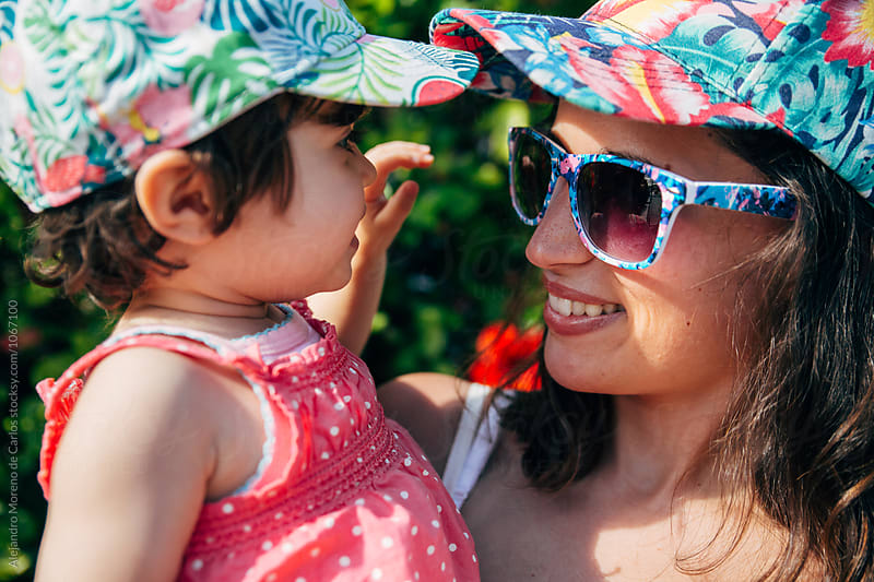 Smiling mother and daughter in tropical-printed caps by Alejandro Moreno de Carlos for Stocksy United