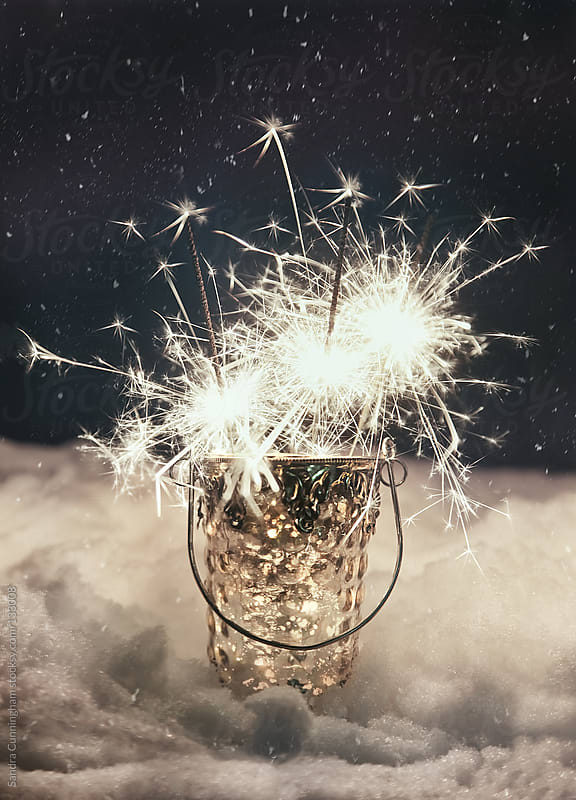Sparklers  in snow at night  by Sandra Cunningham for Stocksy United