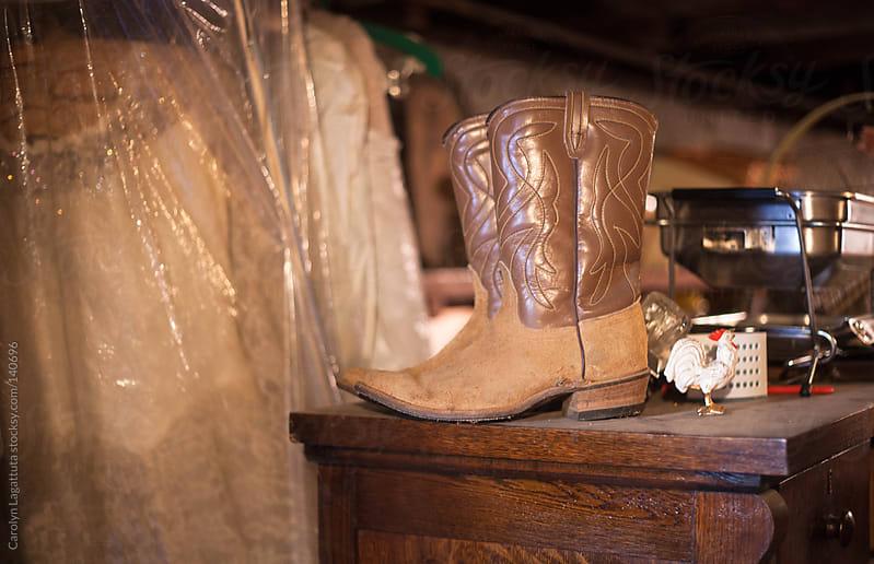 Old cowboy boots and a wedding dress in grandma's basement by Carolyn Lagattuta for Stocksy United
