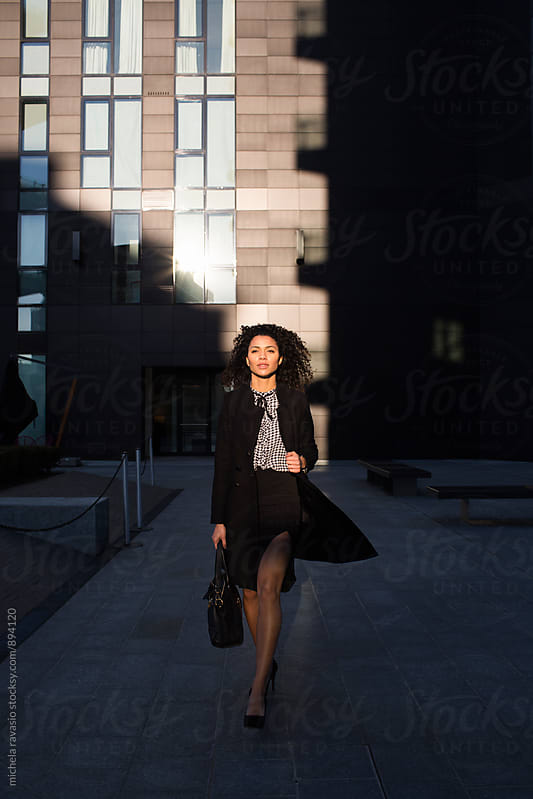 Attractive business woman walking out of office building by michela ravasio for Stocksy United