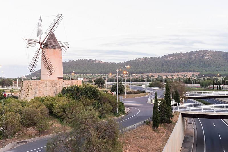 Windmill near a motorway by Marilar Irastorza for Stocksy United