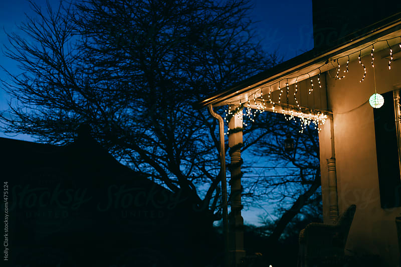 A front porch decorated for Christmas at twilight. by Holly Clark for Stocksy United