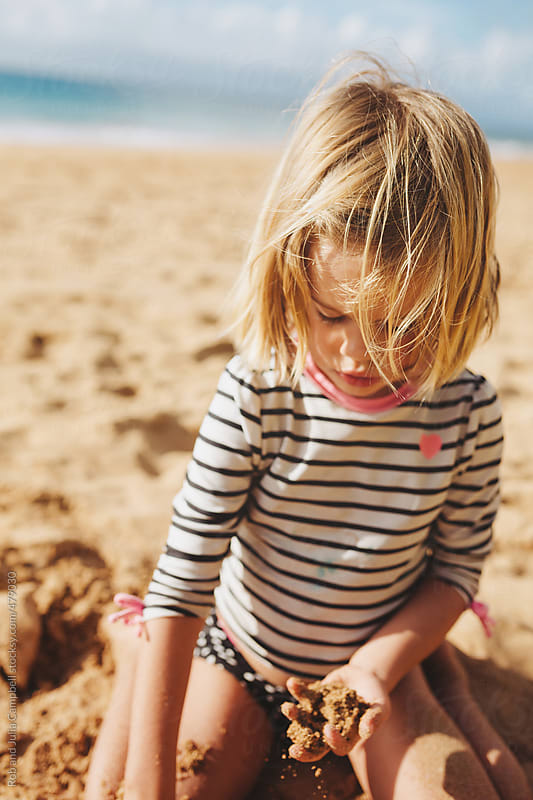 Cute young girl playing in sand on sandy tropical beach in summer by Rob and Julia Campbell for Stocksy United