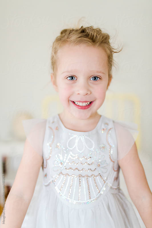headshot of a little girl wearing a fancy dress by Meaghan Curry for Stocksy United