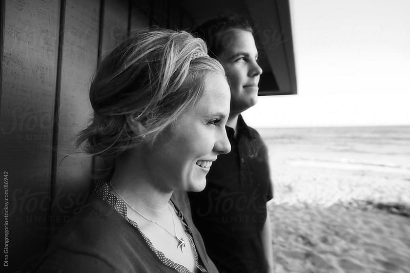Profiles of happy couple at beach looking at scenery by Dina Giangregorio for Stocksy United