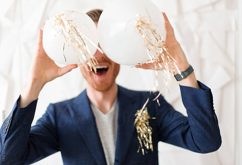 Young man in navy suit having fun laughing smiling at a party acting goofy with balloons by TRU STUDIO for Stocksy United