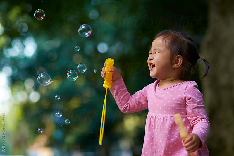 happy little asian girl playing with soap bubble in the park by Bo Bo for Stocksy United