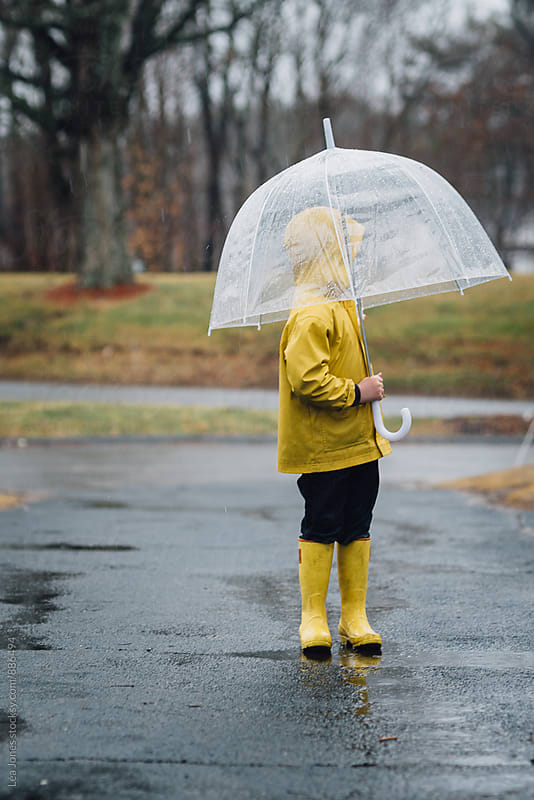 little boy standing under an umbrella in the rain by Léa Jones for Stocksy United