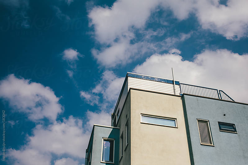 Apartments in Amsterdam with the sky with clouds on thebackground by Ivo de Bruijn for Stocksy United
