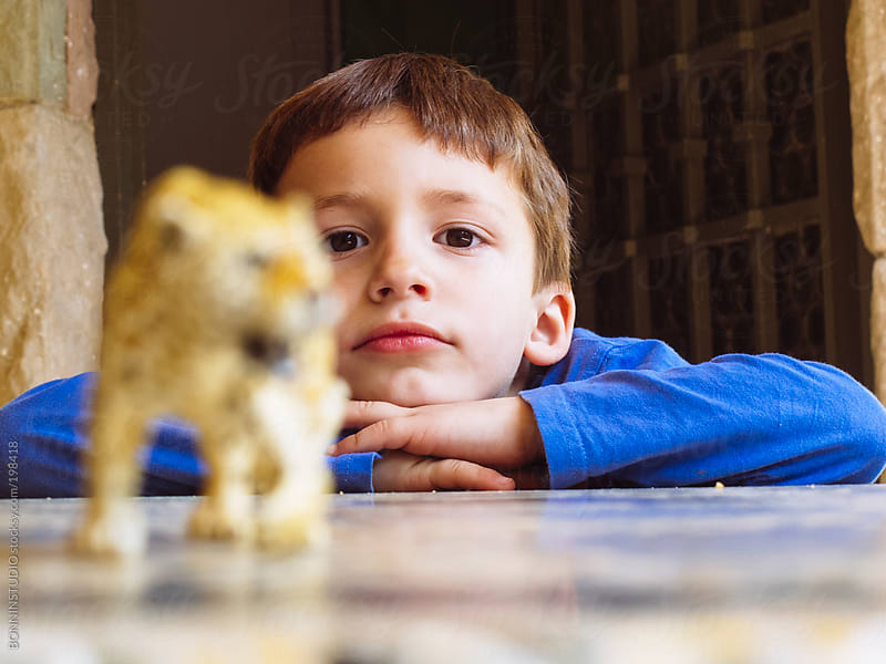Boy playing at home with leopard plastic toy. by BONNINSTUDIO for Stocksy United