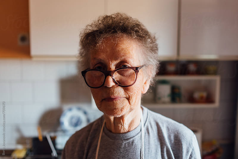 Portrait of senior woman in the kitchen  by Boris Jovanovic for Stocksy United